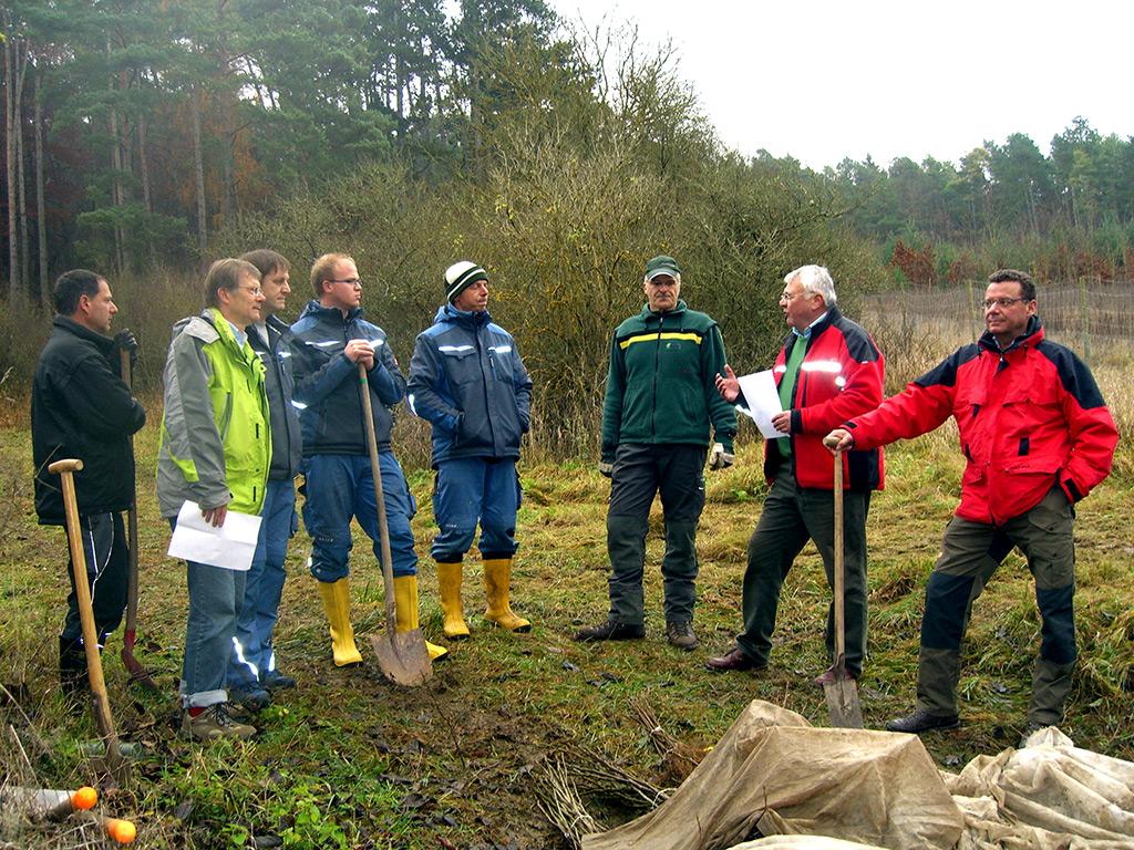 Forstdirektor Jürgen Weihmann (2. von rechts) und Revierleiter Jochen Hellmuth (3. von rechts) stellen die Baumarten vor und geben den Mitarbeitern von TAUBER-SOLAR Tipps für die Pflanzung